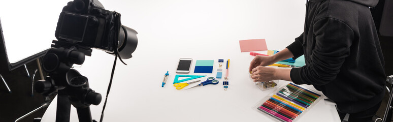 cropped view of female photographer making flat lay with office supplies for commercial photo shooting on white, panoramic shot