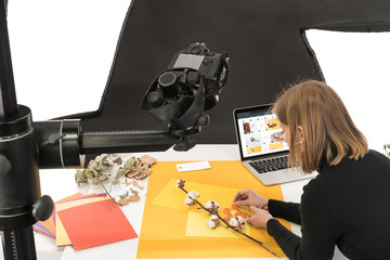 photographer making composition with cotton flower and accessories for photo shooting with camera...