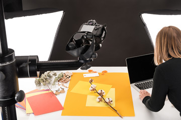 photographer making composition with cotton flower and accessories for photo shooting
