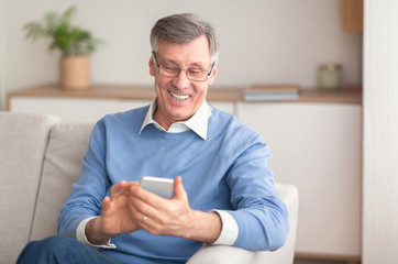 Positive Senior Gentleman Using Phone Sitting On Couch At Home