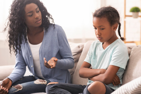 Disappointed black mother looking at her little daughter with reproach