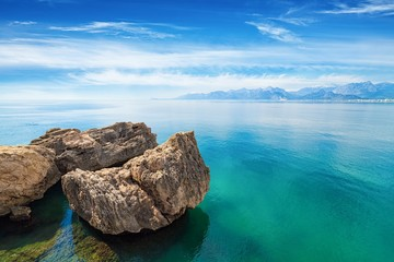 Three cliffs in sea with crystal clear water, blue sky and mountains on horizon near Antalya, Turkey.