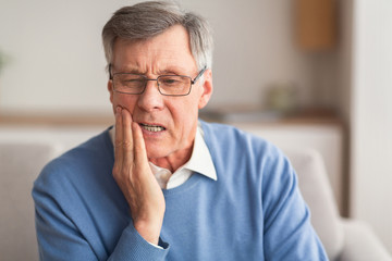 Elderly Man Having Toothache Sitting On Sofa At Home