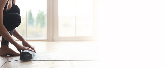 Woman starting her day with meditation, unrolling yoga mat