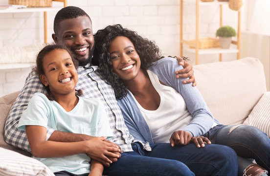 Loving afro family cuddling and smiling to camera at home
