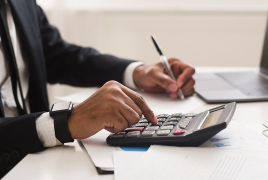 Close up of man checking on incomes, using calculator