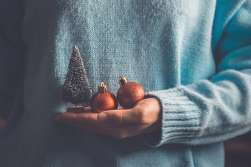 Close up woman hands holding red ball and Christmas tree, Christmas decorative ornament concept