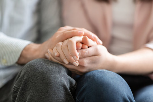 Man and woman holding each other hands, giving psychological support