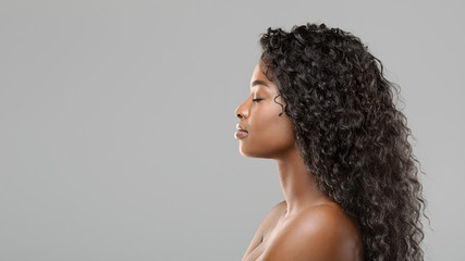Profile portrait of beautiful african american woman with curly long hair