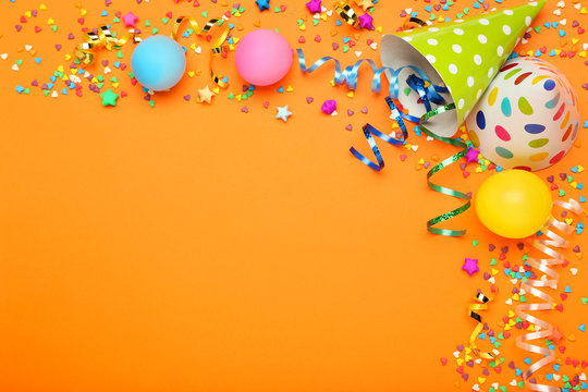 Colorful ribbons with balloons, paper cap and sprinkles on orange background