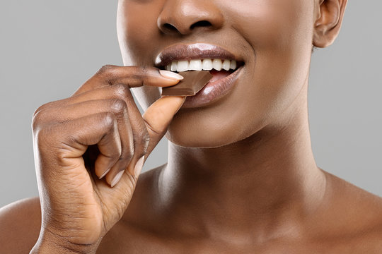 Afro Lady With White Healthy Teeth Biting Milk Chocolate Slice