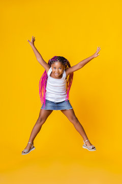 Cute little afro girl jumping over yellow studio background