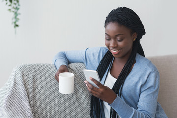 Young afro girl texting on smartphone and drinking coffee at home