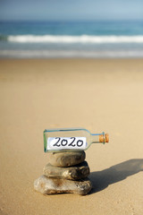 Photo sur Plexiglas Zen pierres a sable Happy New Year 2020 party. Message in a bottle found on the beach on stones in balance. Zen style summer vacation concept.