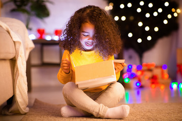 Surprised little african girl opening glowing Christmas gift