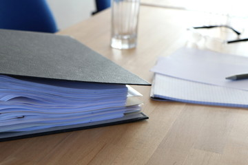 Office scene with file, notebook, glasses and pen on a conference table