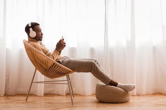 Relaxed Black Man In Headset Using Phone Listening Audiobook Indoor