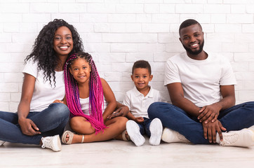 Smiling black parents with two little kids sitting on floor together
