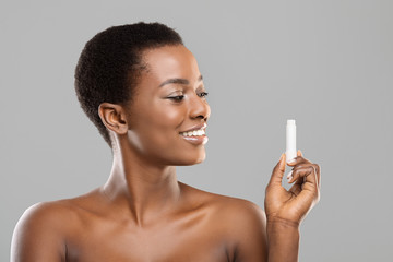 Fototapete - Attractive afro woman holding hygienical chapstick in her hand