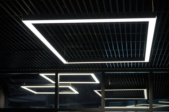 Modern office lighting. Thin lamps in office dark ceiling. LED white cold light over workplaces.