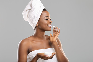 Fototapete - Pretty black woman with perfect skin applying cream to her face