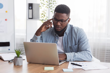 Concerned black employee talking on cellphone and looking at laptop screen