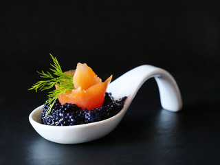 Photo sur Toile Roe Black caviar with smoked salmon bite in white porcelain spoon over black background.