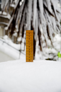 old style ruler measuring snow