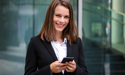 Smiling businesswoman using a smartphone outdoor
