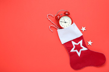 Red christmas stocking with candy canes and alarm clock on red background