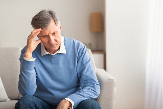 Elderly Man Thinking About Loneliness Sitting On Couch At Home