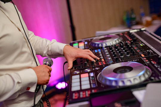DJ plays music at wedding party. Colorful light rays