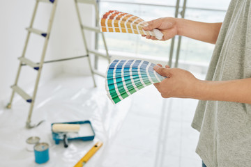 Paper palletes of paint swatches in hands of person choosing color for walls in new apartment