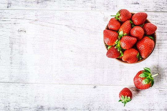 Ripe strawberries forest fruits in wooden bowl on white table. Fresh strawberry top view.