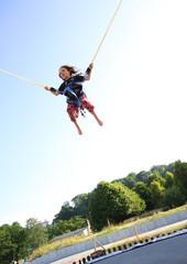 Ein kleines Mädchen springt Bungee auf einem Trampolin