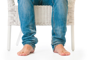 Barefoot man sitting in wicker armchair on white background