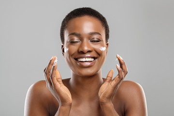 Beautiful afro woman applying cream on her cheeks and sincerely smiling