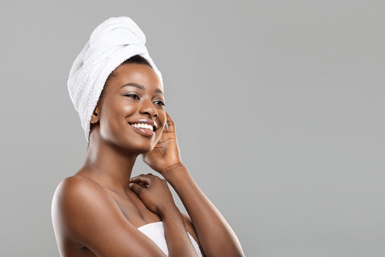 Portrait of afro woman with towel on head and perfect skin