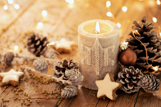 Christmas background - Advent candle with natural Xmas decoration, branches and pine cones on rustic wood
