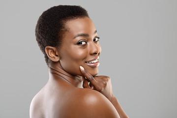 Fototapete - Portrait of flirty black girl seductively looking over shoulder at camera