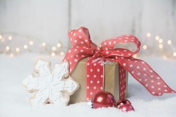 Weihnachtsgeschenk mit roter Schleife im Schnee - Grußkarte