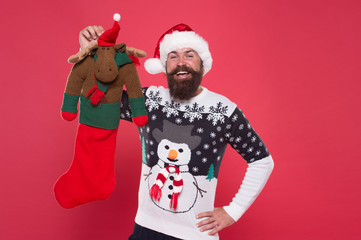 Winter holiday. Check contents of christmas stocking. Man in santa hat hold christmas gift red background. Hipster cheerful face got gift in christmas sock. Christmas stocking concept. Reindeer toy