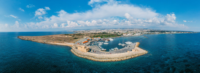 Aerial panorama of Paphos castle from drone in Cyprus. Medieval port castle in harbour on Mediterranean coast.