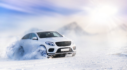 Car drifting on snow in winter mountains. Luxury cars race speed on snowy or ice road with back...