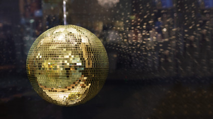 Golden mirror disco ball with bright golden rays, night party background with copy space.