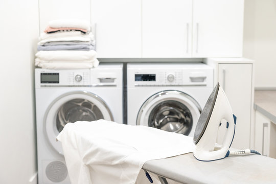 Iron on ironing board with white shirt in laundry room