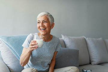 Senior woman's hands holding a glass of milk. Happy senior woman having fun while drinking milk at...