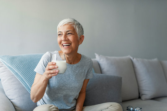 Senior woman's hands holding a glass of milk. Happy senior woman having fun while drinking milk at home. Senior Woman drinking a glass of milk to maintain her wellbeing.....