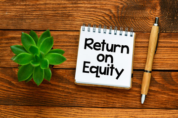 Return on equity text in a small notebook on a wooden background. Top view, high quality photo and quality for business use.
