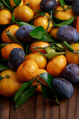 fresh mandarines and plums on wooden background